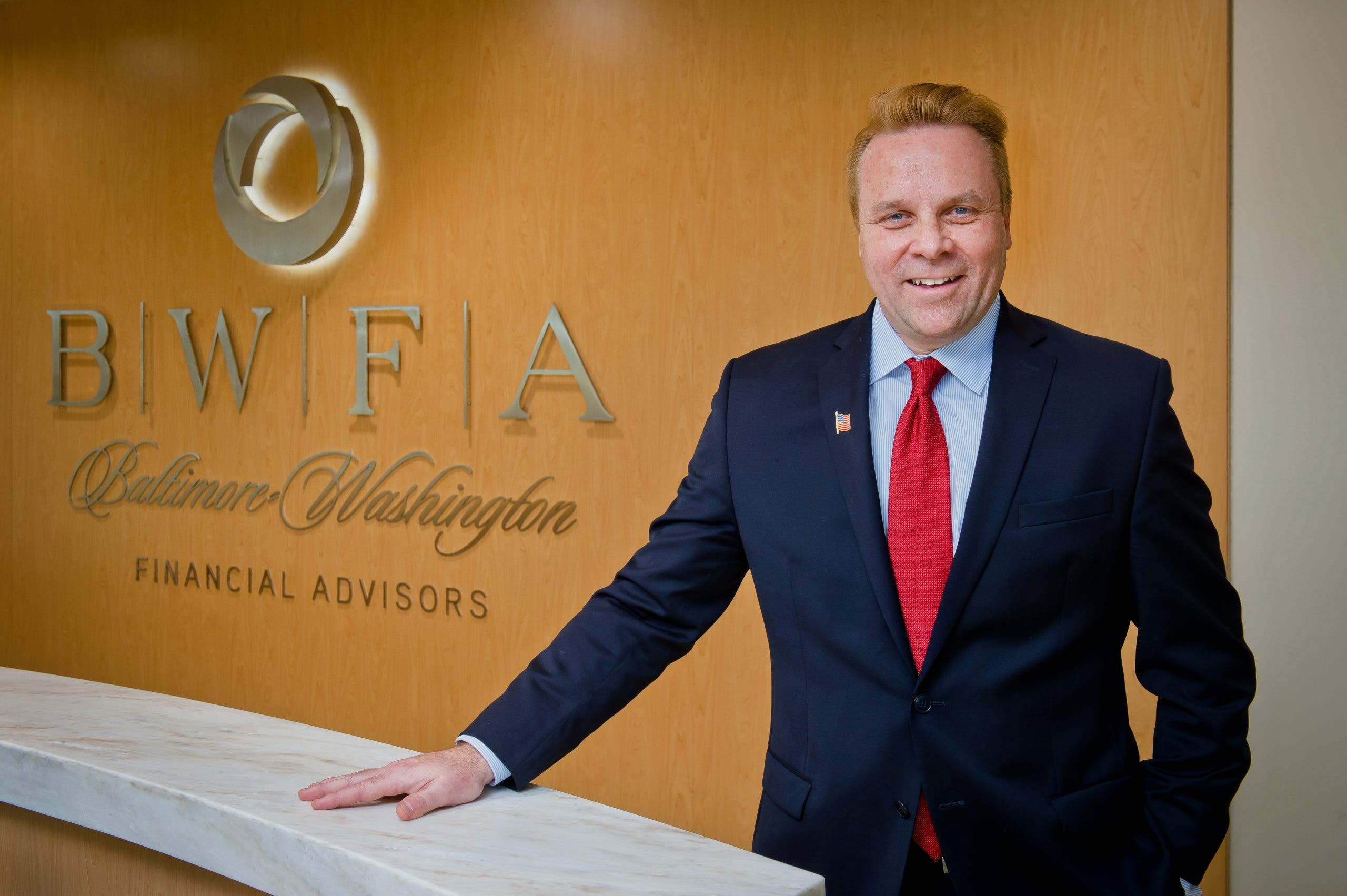 Rob Carpenter stands in front of Baltimore Washington Financial Advisors sign